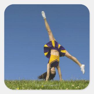 Female cheerleader doing cartwheel square sticker