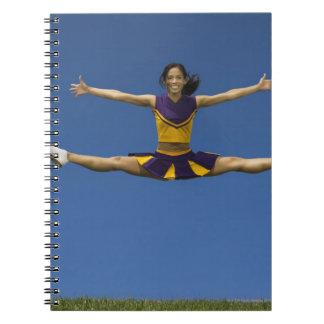 Female cheerleader doing jump splits in air 2 note books