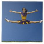 Female cheerleader doing jump splits in air 2 large square tile