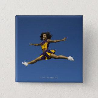 Female cheerleader doing jump splits in air button