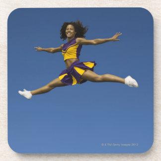 Female cheerleader doing jump splits in air coaster