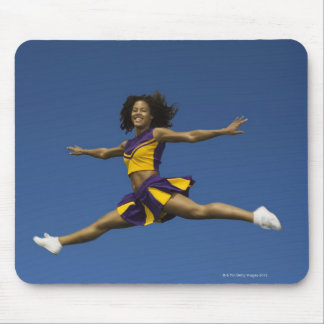 Female cheerleader doing jump splits in air mouse pad