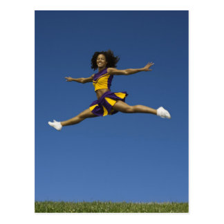 Female cheerleader doing jump splits in air postcard