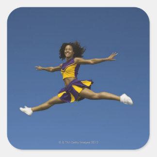 Female cheerleader doing jump splits in air square sticker
