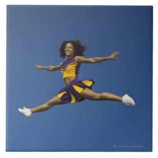 Female cheerleader doing jump splits in air tile