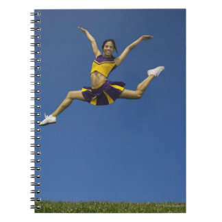 Female cheerleader jumping in air, arms note books