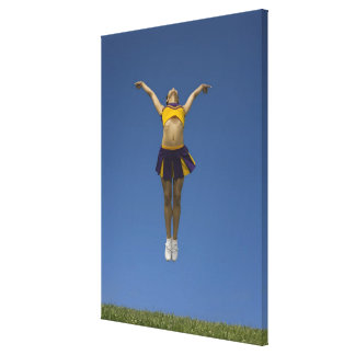 Female cheerleader jumping in air, front view canvas print