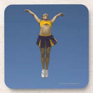 Female cheerleader jumping in air, front view drink coaster