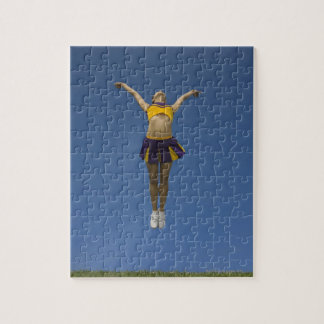 Female cheerleader jumping in air, front view jigsaw puzzle