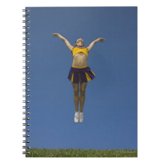Female cheerleader jumping in air, front view notebooks