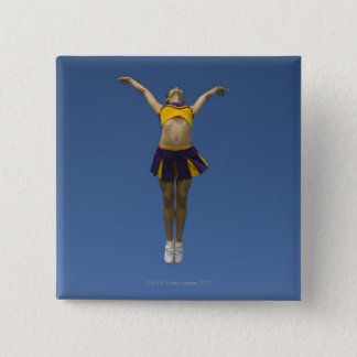 Female cheerleader jumping in air, front view pinback button