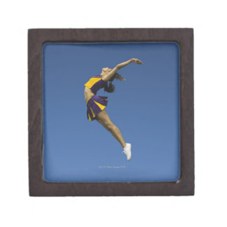 Female cheerleader jumping in air, side view gift box