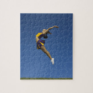 Female cheerleader jumping in air, side view jigsaw puzzle