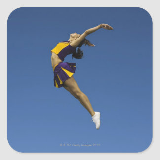 Female cheerleader jumping in air, side view square sticker