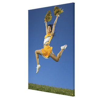 Female cheerleader jumping in air with pompoms canvas print