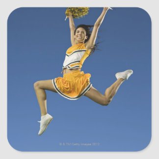Female cheerleader jumping in air with pompoms square sticker