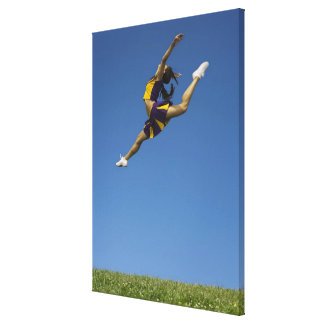 Female cheerleader leaping high up in air canvas print