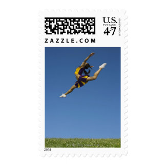 Female cheerleader leaping high up in air postage stamp