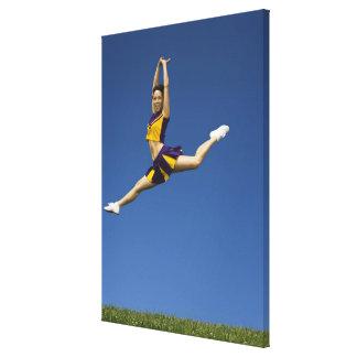 Female cheerleader leaping in air canvas print