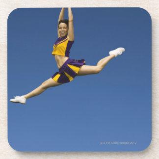Female cheerleader leaping in air coaster