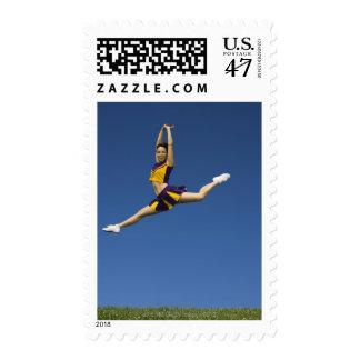 Female cheerleader leaping in air postage