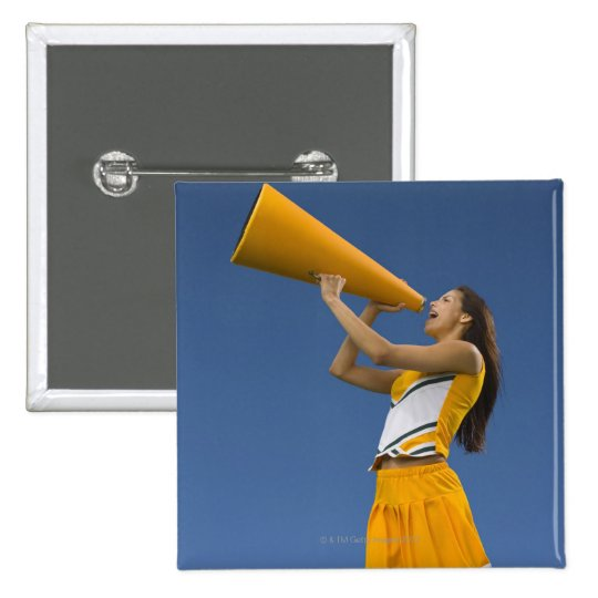 Female cheerleader shouting into megaphone button