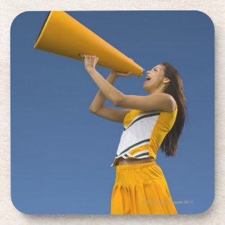 Female cheerleader shouting into megaphone coaster