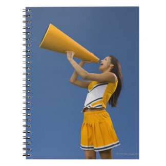 Female cheerleader shouting into megaphone note books