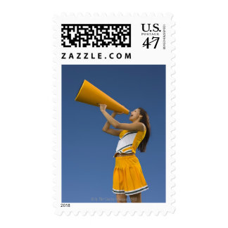 Female cheerleader shouting into megaphone postage
