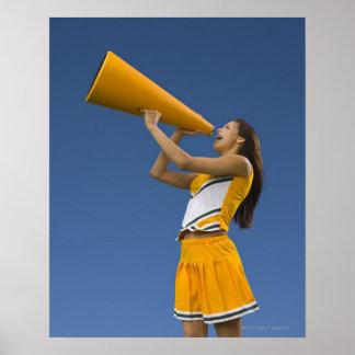 Female cheerleader shouting into megaphone poster