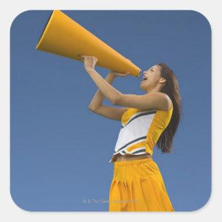 Female cheerleader shouting into megaphone square sticker