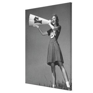 Female cheerleader using megaphone canvas print