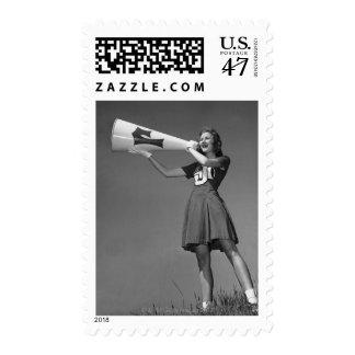 Female cheerleader using megaphone postage