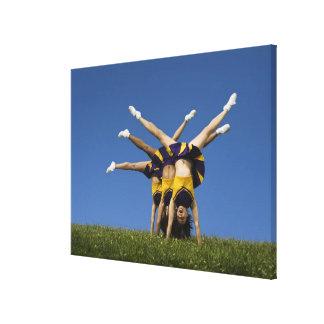 Female cheerleaders doing handstands canvas print