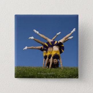 Female cheerleaders doing handstands pinback button