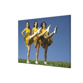 Female cheerleaders doing high kicks canvas print
