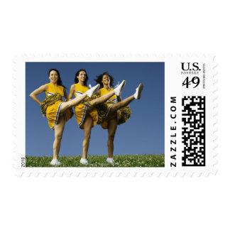 Female cheerleaders doing high kicks stamp