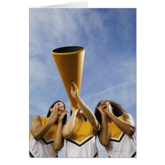 Female cheerleaders shouting through megaphone, card