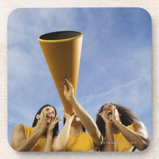Female cheerleaders shouting through megaphone, drink coaster