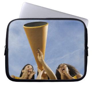 Female cheerleaders shouting through megaphone, laptop computer sleeve