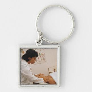 Female chiropractor massaging a patient keychain