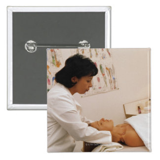 Female chiropractor massaging a patient pinback button