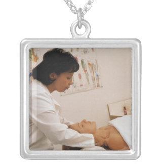 Female chiropractor massaging a patient square pendant necklace