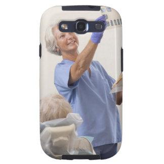 Female dental hygienist examining an X-Ray Galaxy SIII Covers