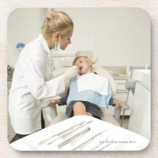 Female dentist examining little boy coaster