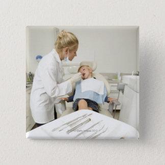 Female dentist examining little boy pinback button