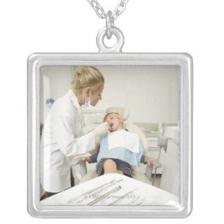 Female dentist examining little boy silver plated necklace