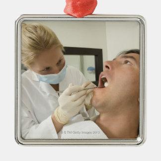 Female dentist examining man metal ornament