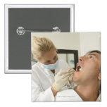 Female dentist examining man pinback button