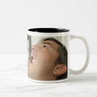 Female dentist examining man Two-Tone coffee mug